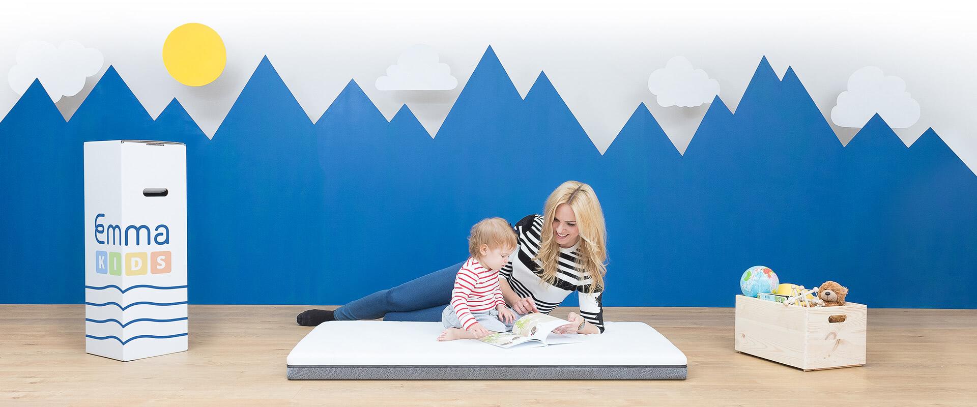 Moeder leest voor aan kind op een matras